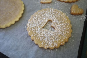sprinkling confectioners' sugar on linzer cookies
